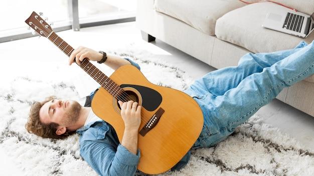 床に座ってギターを弾く男