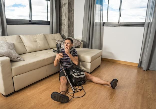 거실 바닥에 앉아 있는 남자가 진공 청소기가 어떻게 작동하는지 이해하려고 합니다. 전신.