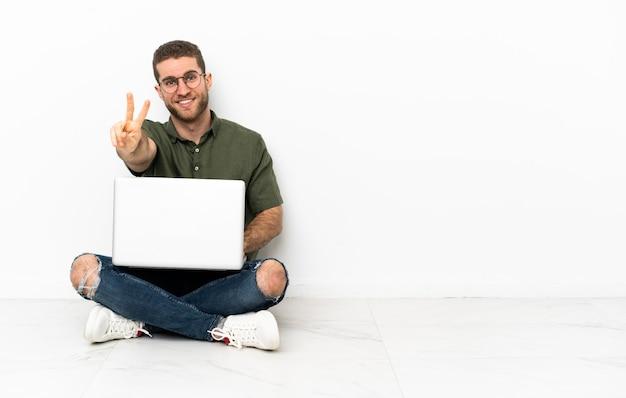 노트북으로 바닥에 앉아 있는 남자