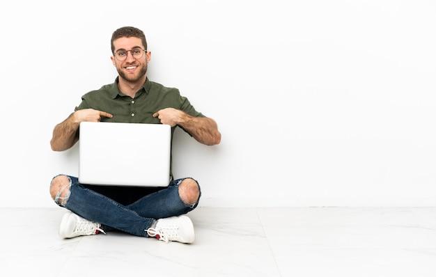 Человек сидит на полу с ноутбуком