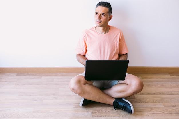 Человек сидит на полу со своим ноутбуком, работая удаленно из дома