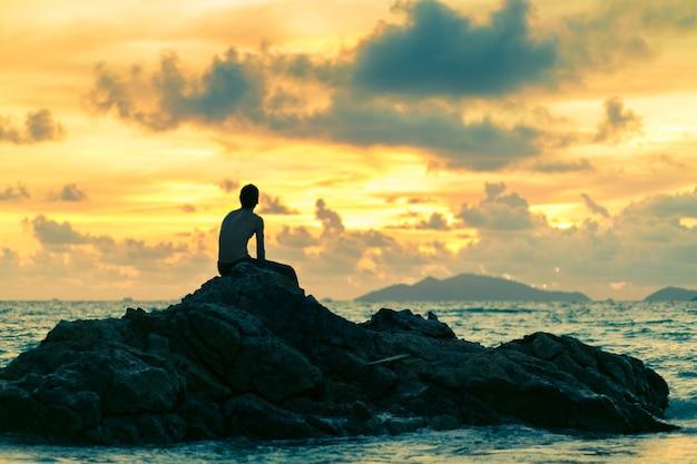 Человек сидит на скале на пляже на фоне заката