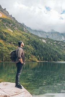 ビューハイキングの概念を楽しんで山の湖の前の岩の上に座っている男