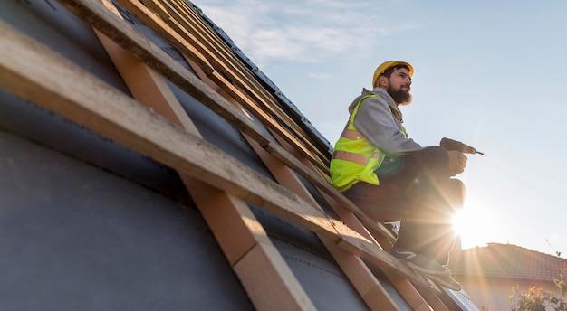 日光の下で屋根に座っている男