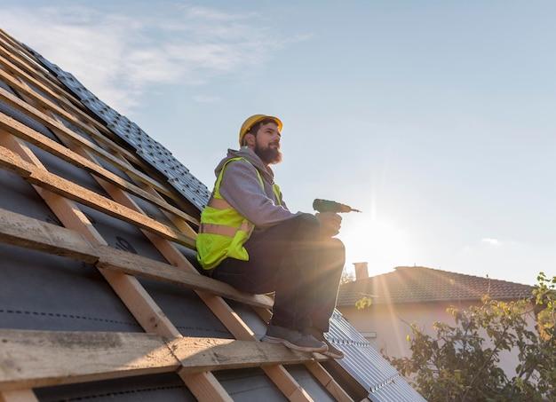 屋根の上に座っている男
