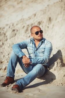 Человек сидит на песке в очках