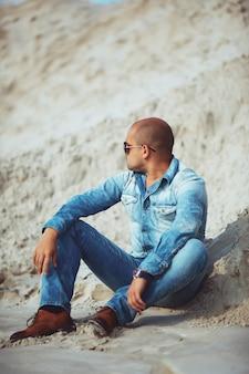 Человек сидит на песке в очках смотрит в сторону