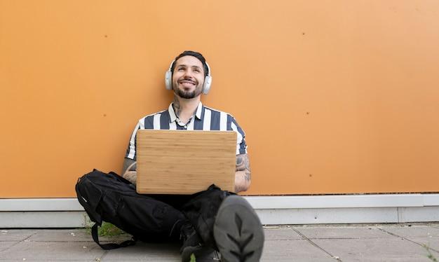 ノートパソコンとヘッドフォンで通りに座っている男幸せな笑顔