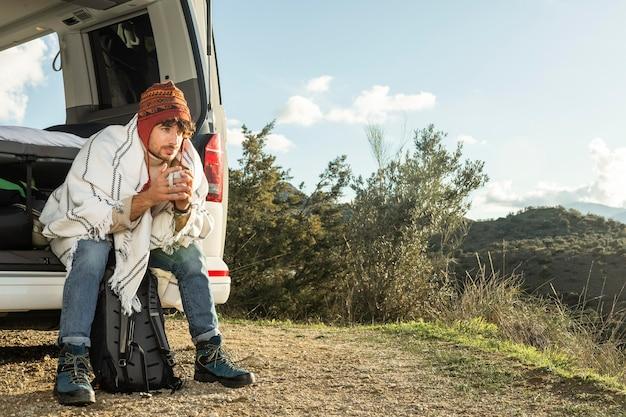 복사 공간이있는 도로 여행을하는 동안 차 트렁크에 앉아있는 남자