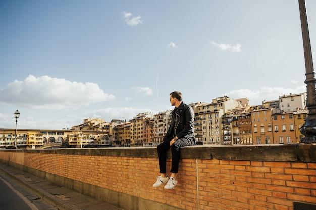 Человек сидит на стене возле реки арно с красочным старым мостом сзади.