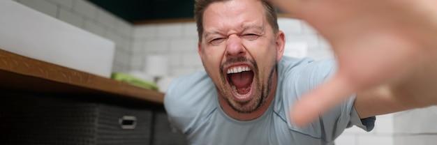 トイレに座って痛みで叫んでいる男