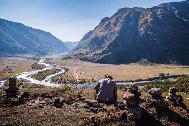 산 강 계곡의 보기와 함께 위에 앉아 남자. 러시아, 알타이, chulyshman 강
