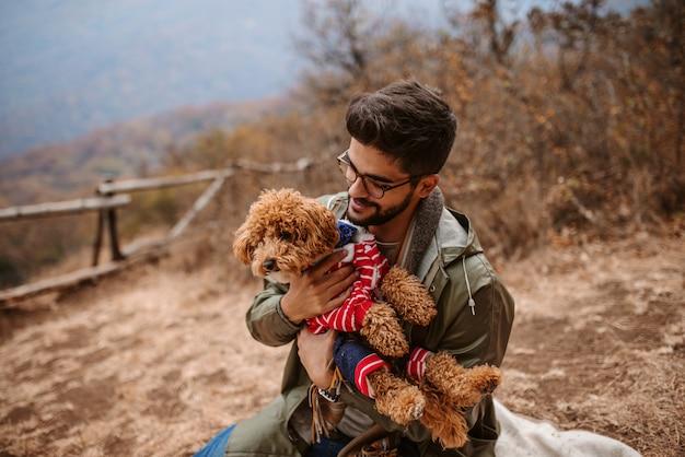 Человек сидит на улице и держит собаку.