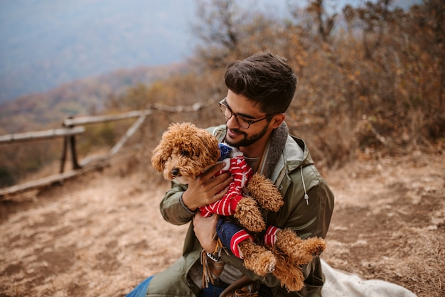 Man sitting outdoors and holding dog.