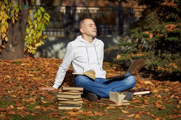 Man sitting in  park with laptop notepad books and textbooks outdoor learning social distancing