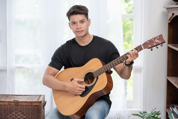 A man sitting and playing guitar on a chair.