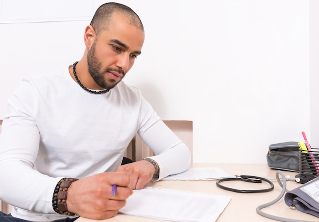 Man sitting proof reading or checking a report