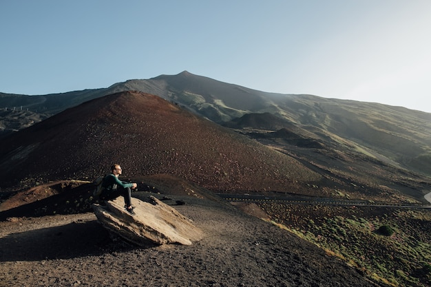 Man sitting on rock and enjoying beautiful landscape of volcano etna in sicily