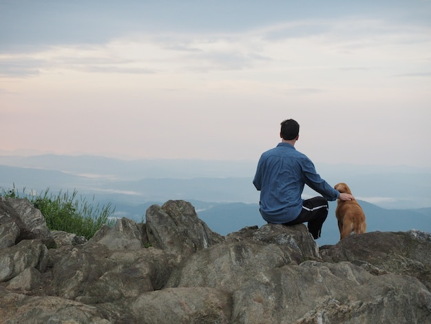 Man sitting on the rock and petting a dog surrounded by mountains under a cloudy sky