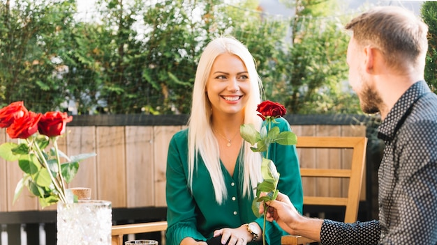Man sitting at rooftop giving red rose to her smiling girlfriend