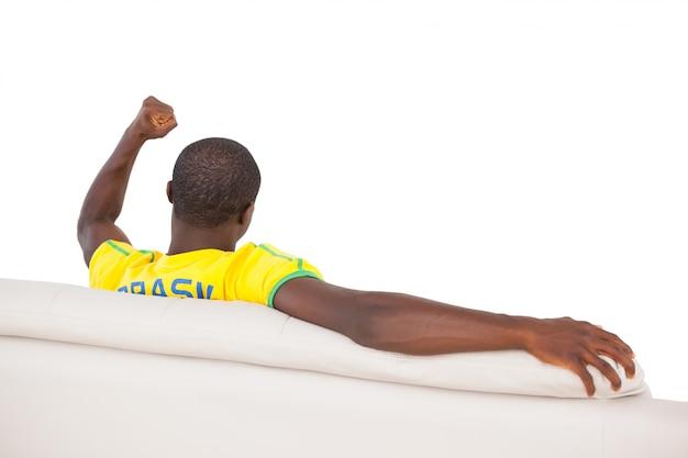 Man sitting on sofa and cheering