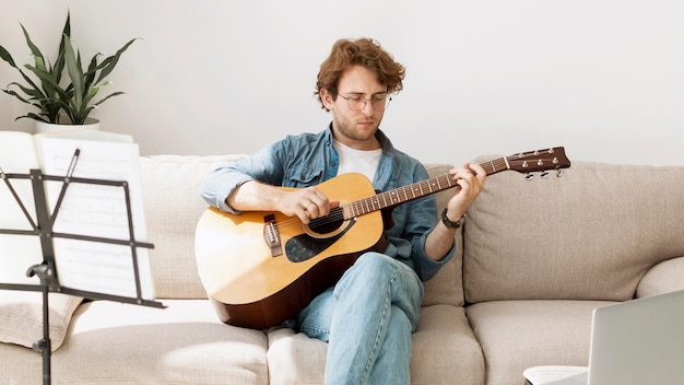 Man sitting on sofa and learning guitar