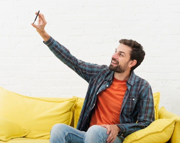 Man sitting on sofa and taking selfies