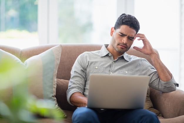 Man sitting on sofa and using laptop in living room at home