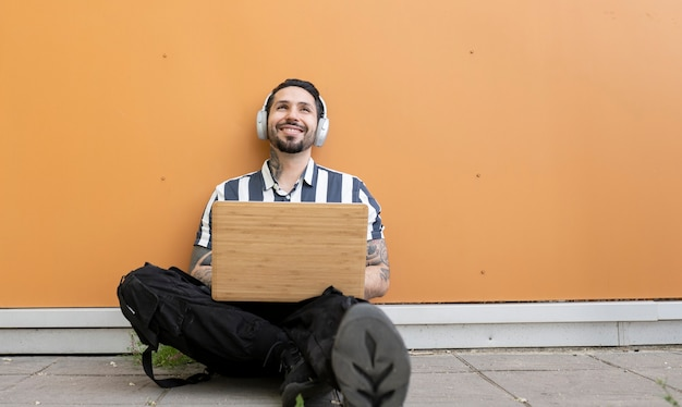 Man sitting on the street with laptop and headphones happy smiling