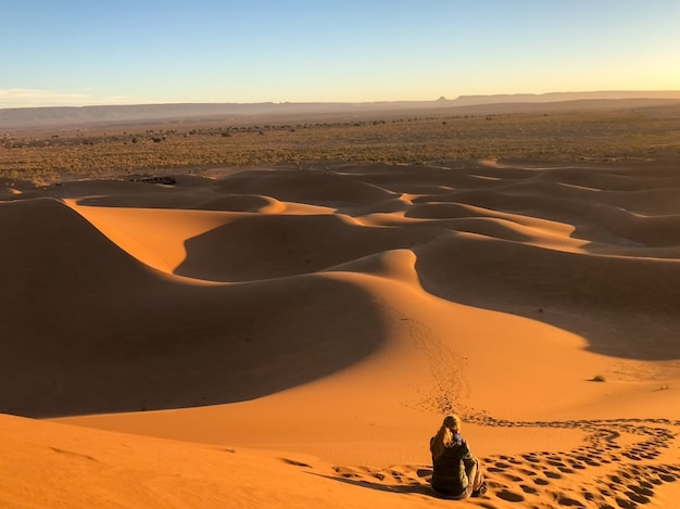 Man sitting on sun dunes at a desert surrounded by tracks