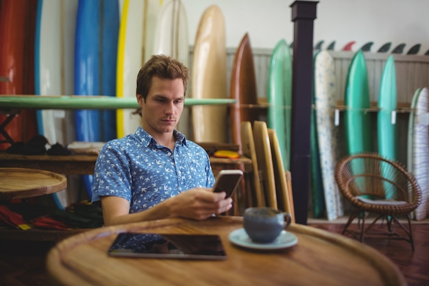 Man sitting in surfboard shop