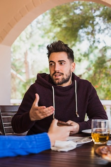 Man sitting at table outdoors talking with person