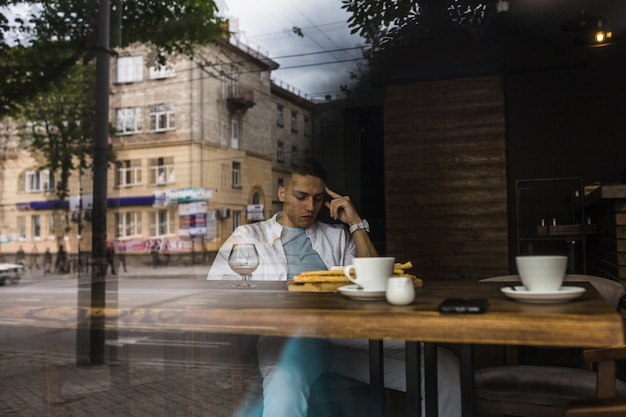 Man sitting at table in restaurant seen from window glass