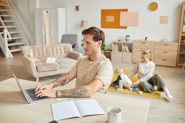 Man sitting at the table and working on laptop with his family playing  at home