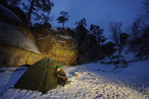 Man sitting in tent at the mountain base camp