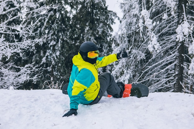 Man sitting on the top of the hill with snowboard looking at hill with forest extreme lifestyle