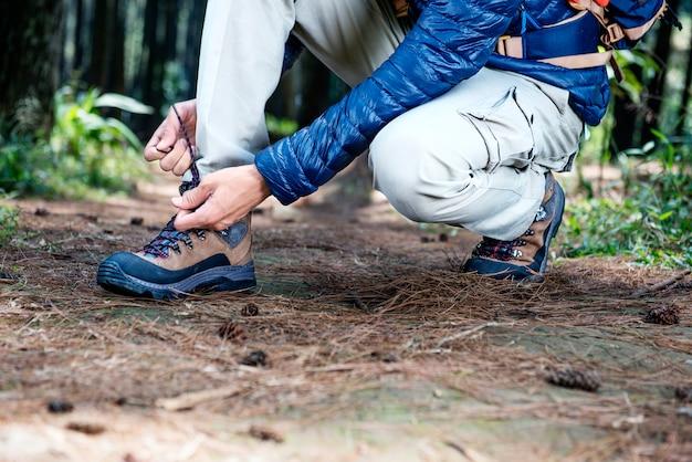 Man sitting and tying his trekking shoelace