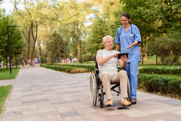 Man sitting in a wheelchair and shows nurse something.