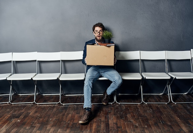 Man sitting on white chair waiting for lighting box job search depression