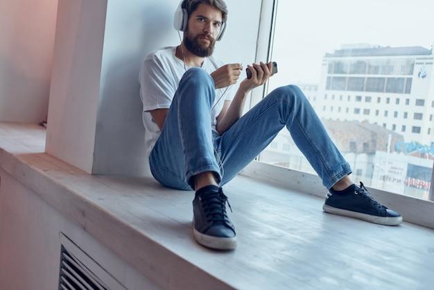 Man sitting on the windowsill in headphones in headphones communication