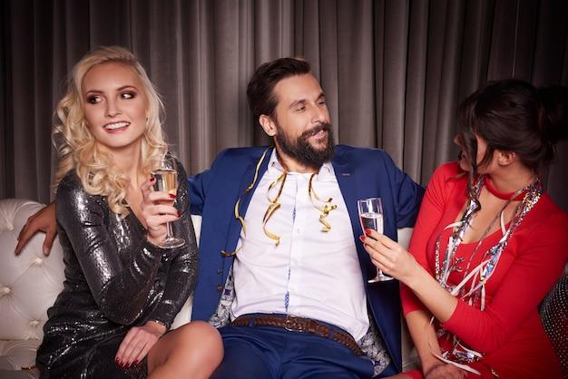 Мужчина сидит с привлекательными женщинами на диване