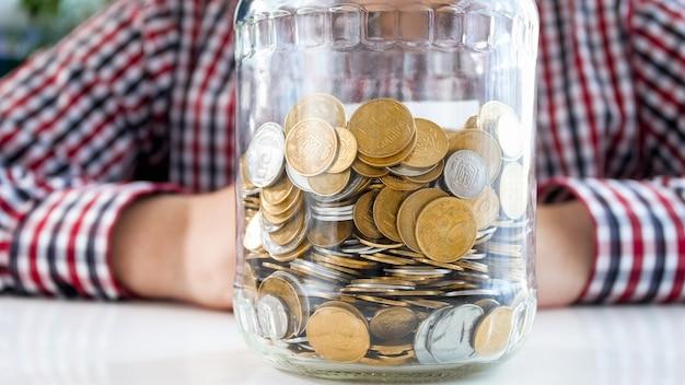 동전의 전체 유리 항아리와 함께 앉아 남자입니다. 금융, 경제 성장 및 은행 저축의 개념.