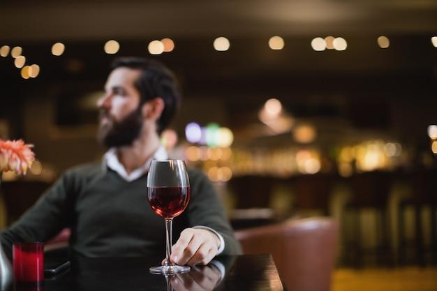 ワインのグラスで座っている男