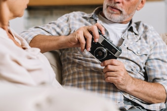 Man sitting with her wife holding camera in hand