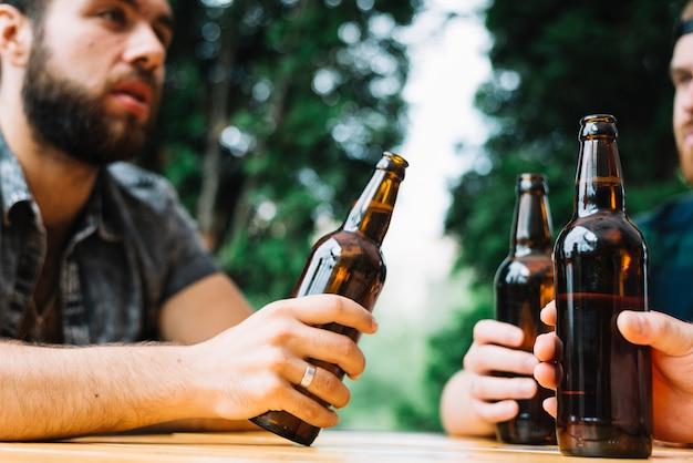 屋外で茶色のビール瓶を持っている彼の友人と座っている男