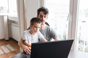 Man sitting with his son using laptop