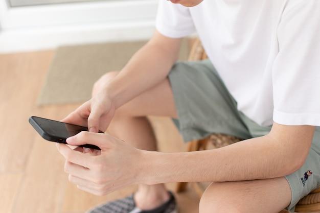 手に黒い電話を再生して座っている男
