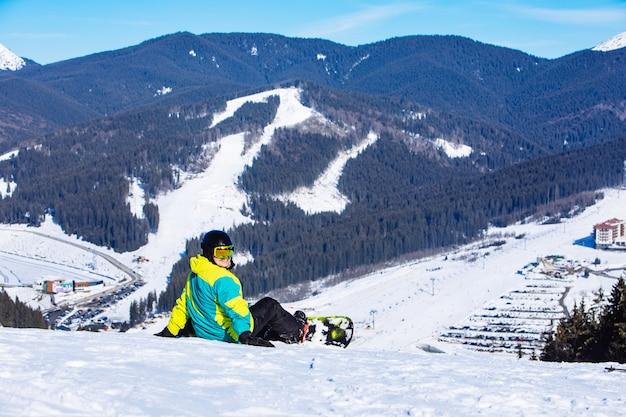 Человек сидит со сноубордом на вершине холма с прекрасным видом. копировать пространство. солнечный день
