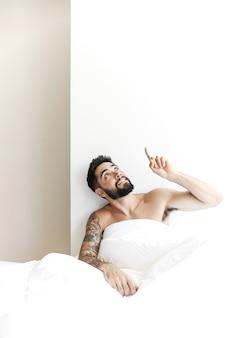 Man sitting with white blanket pointing upward