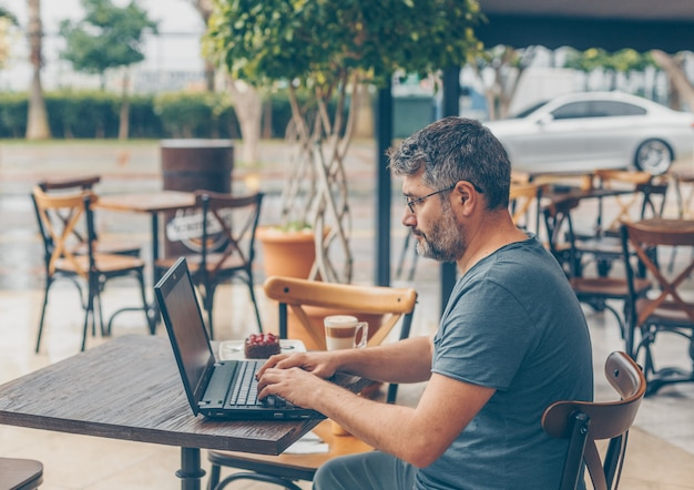 Man sitting and working on laptop in cafe terrace during daytime and looking busy